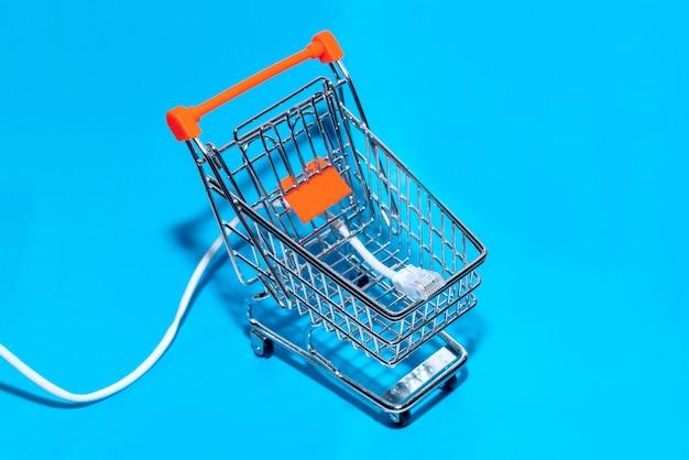 Netwerkkabel in de winkelwagen blauwe achtergrond. bovenaanzicht met kopie ruimte. selectieve aandacht. Premium Foto