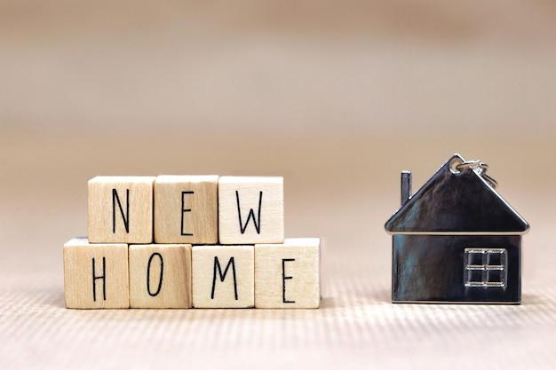 New home-tekst geschreven met houten kubussen met gezellig huisje Premium Foto