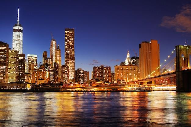 New york city brooklyn bridge en downtown skyline over east river in de nacht Premium Foto