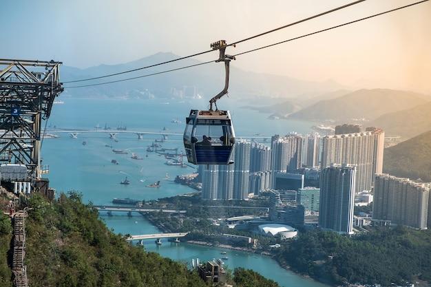 Ngong ping-kabelwagen met toeristen over haven, bergen en stadsachtergrond in hong kong Premium Foto