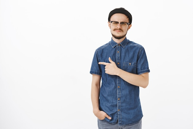 Niet onder de indruk kieskeurige europese man met baard in glazen trendy muts en blauw shirt grijnzend en fronsend van afkeer om onzorgvuldig en ontevreden te zijn, wijzend naar iets niet indrukwekkend Gratis Foto