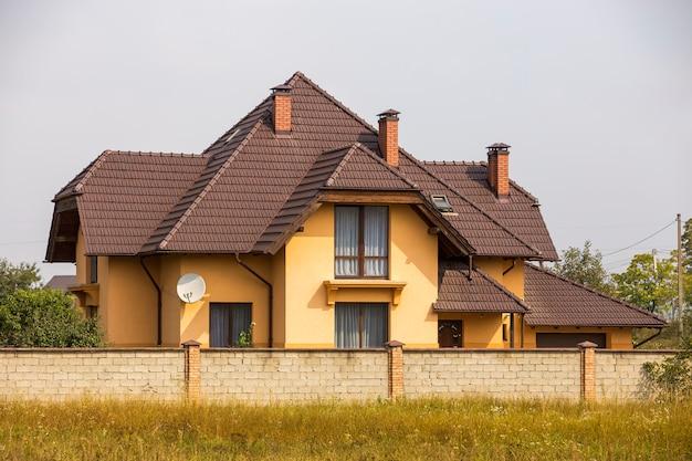 Nieuw comfortabel twee verdiepingen tellend huisje met steile grinddak, satellietschotel op stucwerk muur, Premium Foto