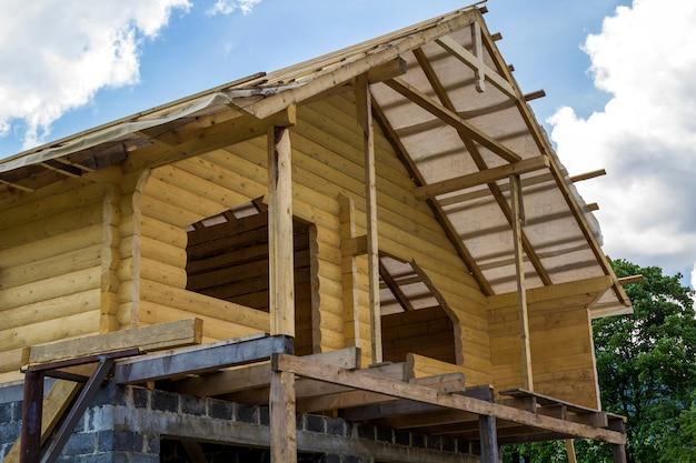 Nieuw huisje van natuurlijke houtmaterialen in aanbouw. houten muren en dak op hoge stenen garage. vastgoed, investeringen, professioneel bouwen en wederopbouwconcept. Premium Foto