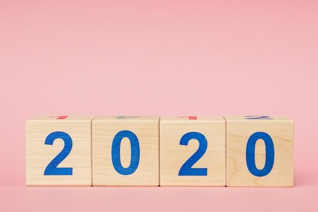 Nieuw jaar 2020 concept. houten blok kubus met nummer op roze tafel Premium Foto