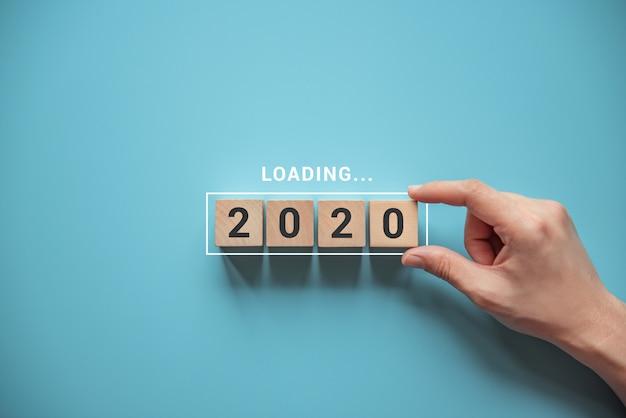 Nieuw jaar 2020 laden met hand die houten kubus in voortgangsbalk zet. Premium Foto