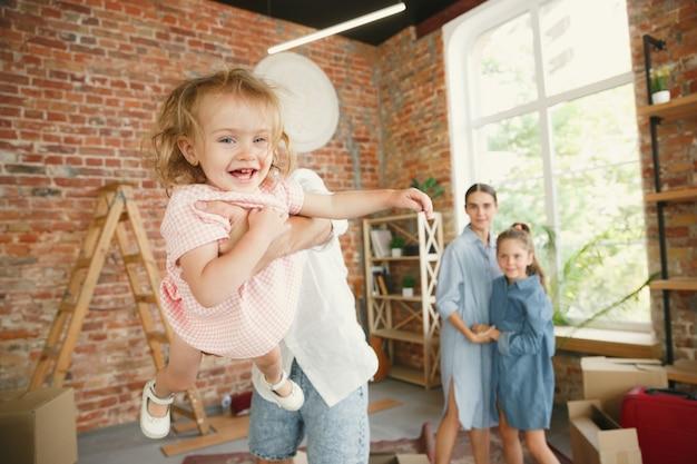 Nieuw leven. volwassen gezin verhuisde naar een nieuw huis of appartement. echtgenoten en kinderen zien er gelukkig en zelfverzekerd uit. verhuizen, relaties, nieuw levensconcept. dozen met hun spullen uitpakken, samen spelen. Gratis Foto