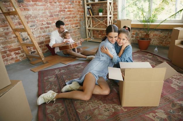 Nieuw leven. volwassen gezin verhuisde naar een nieuw huis of appartement. echtgenoten en kinderen zien er gelukkig en zelfverzekerd uit Gratis Foto