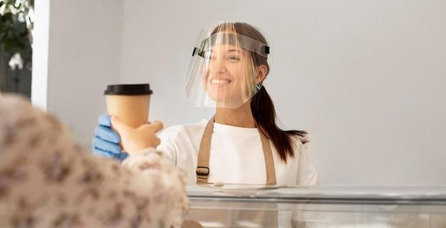 Nieuw normaal bij de coffeeshop met gezichtsscherm Gratis Foto