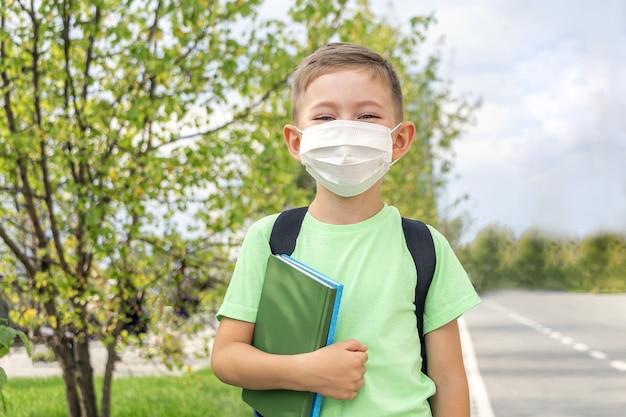 Nieuw normaal, terug naar school. schooljongen die medisch masker en rugzak draagt die leerboek in openlucht houdt Premium Foto