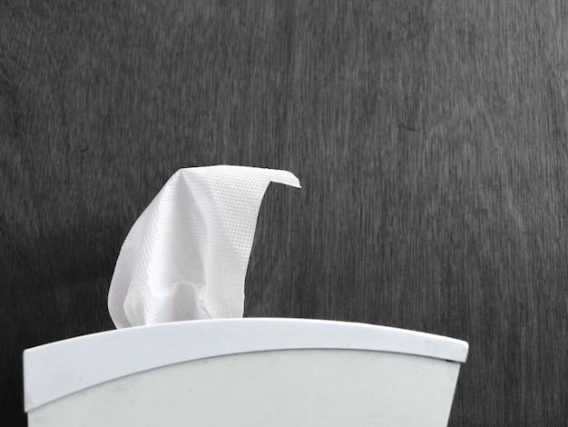 Nieuw wit weefsel op doos met donkere houten muurachtergrond. Premium Foto
