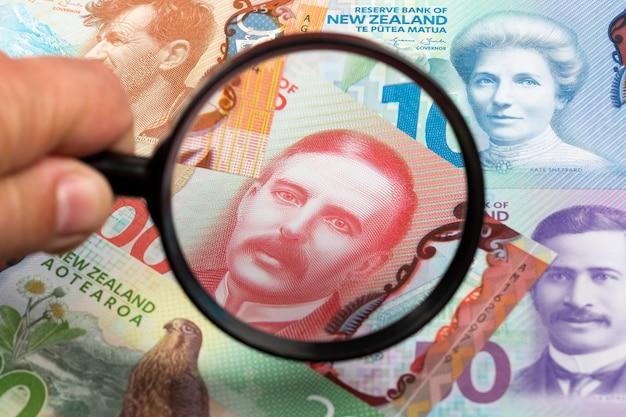 Nieuw-zeelandse dollars op een vergrootglasachtergrond Premium Foto