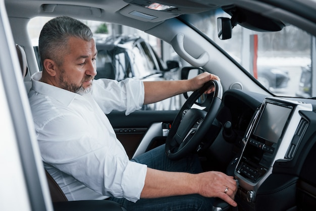Nieuwe auto kopen en testen. senior zakenman in officiële kleding zit in een luxeauto en het indrukken van de knoppen op de muziekspeler Gratis Foto