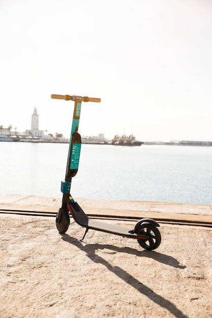 Nieuwe elektrische scooters geparkeerd in de buurt van het dok tegen de idyllische zee Gratis Foto