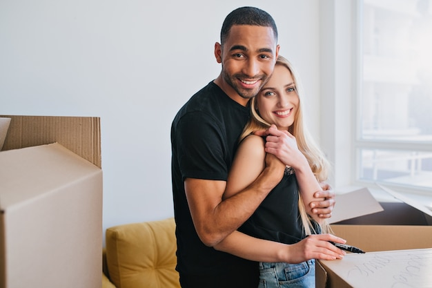 Nieuwe familie gaat verhuizen in een nieuw appartement, vrolijk paar inpakken voor verhuizing. jonge man en vrouw knuffelen, ze rond dozen in lege ruimte. vrijetijdskleding dragen. Gratis Foto