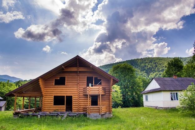 Nieuwe houten ecologische huisje met balkon, terras, steile dak van natuurlijke materialen in aanbouw op grasweide op beboste heuvels. oude tradities en modern bouwconcept. Premium Foto
