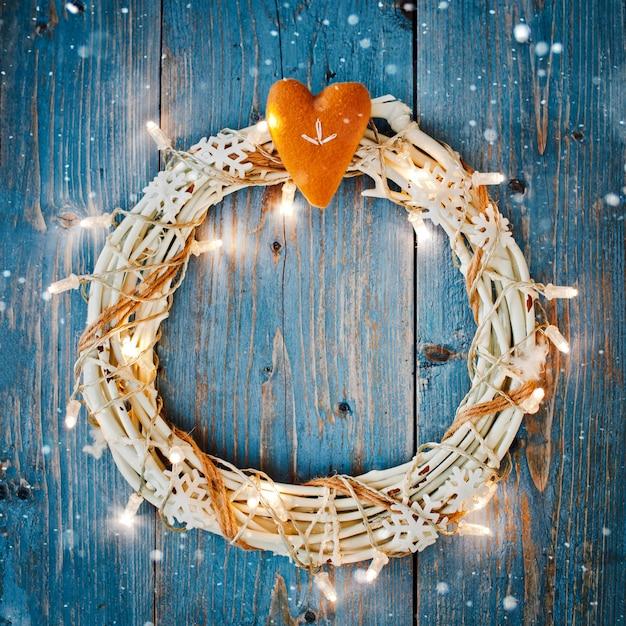 Nieuwe jaardecoratie rond de lege ruimte van de kerstmisbrief voor slingers van tekst de brandende lichten op blauwe houten achtergrond. Premium Foto