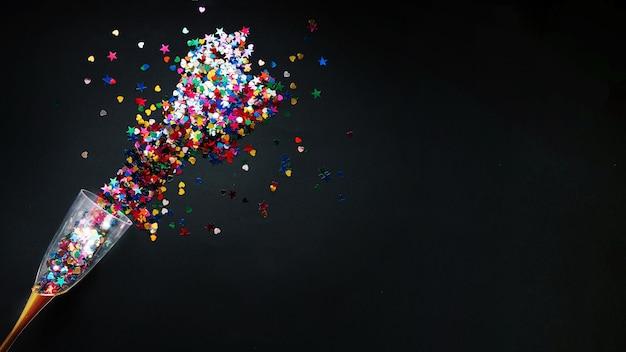 Nieuwe jaarsamenstelling met kleurrijke confettien in glas Gratis Foto
