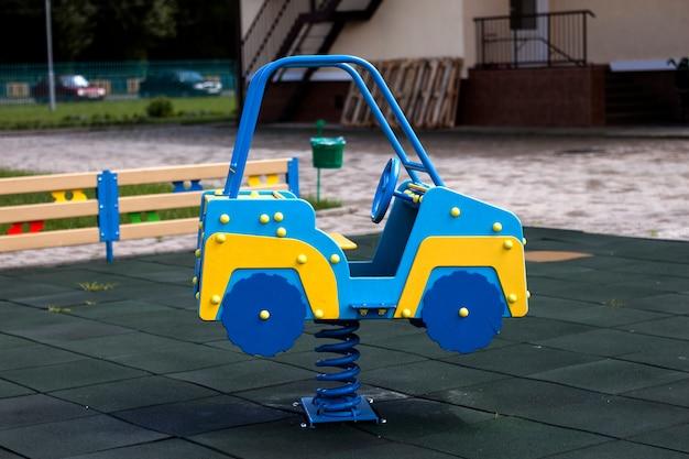 Nieuwe moderne plastic heldere kleurrijke blauwe en gele grote speelgoedauto op lente op kwekerij speeltuin met zachte rubberen vloeren op heldere zonnige zomerdag. perfecte plek voor buitenactiviteiten voor kinderen. Premium Foto