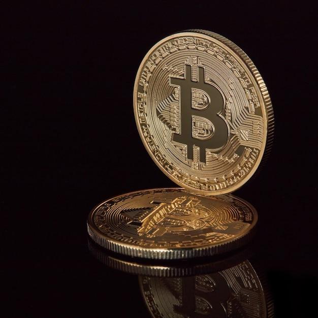 Nieuwe virtuele geld gestapelde cryptovaluta gouden bitcoins-munten op zwart reflecterend oppervlak Premium Foto