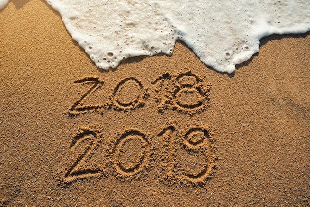 Nieuwjaar 2019 komt er aan. gelukkig nieuwjaar 2019 vervangt 2018-concept op het zee strand Premium Foto