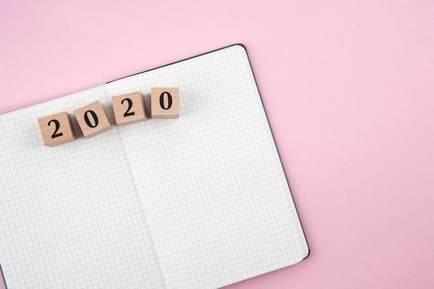 Nieuwjaar 2020-notitieboekje op roze achtergrond Premium Foto