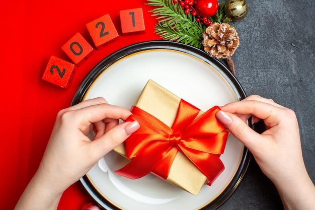 Nieuwjaar achtergrond met cadeau op diner plaat decoratie accessoires fir takken en nummers op een rood servet op een zwarte tafel Gratis Foto