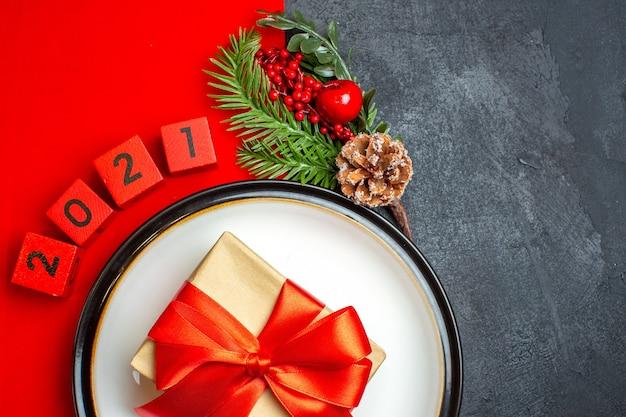 Nieuwjaar achtergrond met mooi cadeau op een diner plaat decoratie accessoires fir takken en cijfers op een rood servet op een zwarte tafel half shot foto Gratis Foto