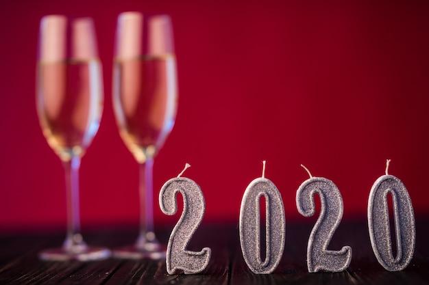 Nieuwjaar decoratie. twee gobelts met champagne met decoratie van kerstmis of nieuwjaar 2020 op rode lichte achtergrond Gratis Foto