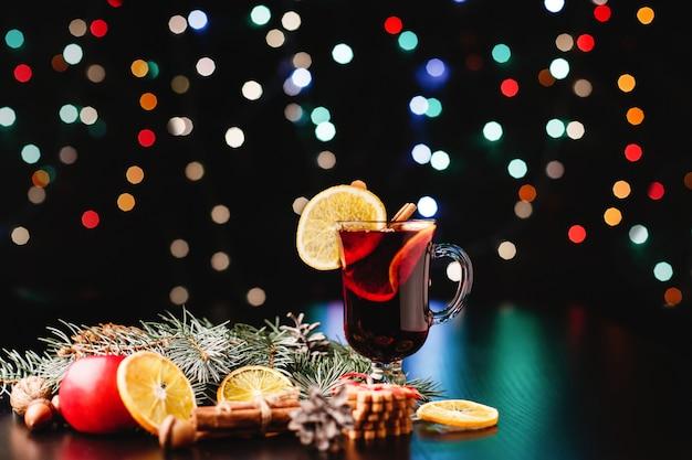 Nieuwjaar en kerstmis decor. glazen met glühwein staan op tafel met sinaasappels, appels Gratis Foto