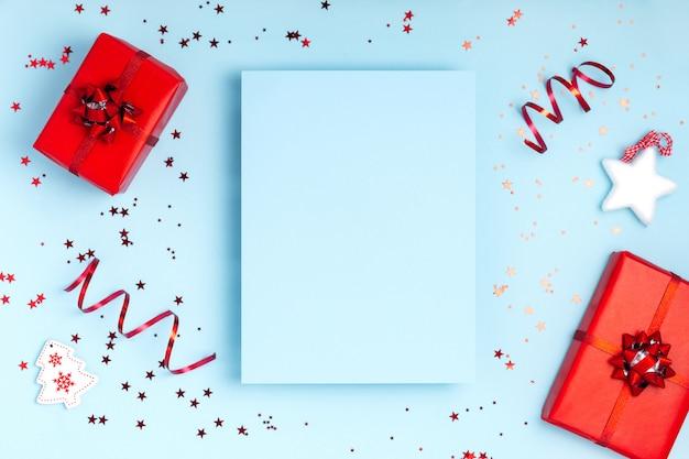Nieuwjaar en kerstmis winter creatieve frame samenstelling. blanco vel papier, geschenkdozen en schittert op pastel blauwe achtergrond. bovenaanzicht, plat lag, kopie ruimte. sjabloonontwerp uitnodigingskaart Premium Foto