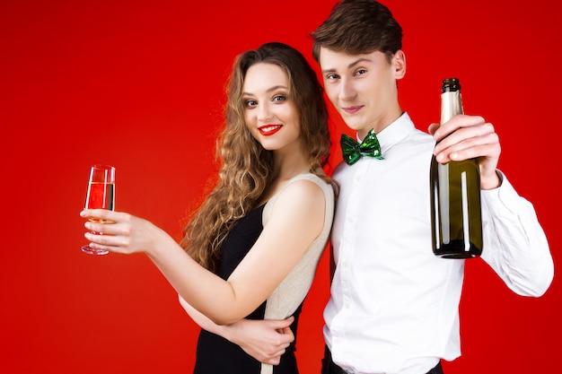 Nieuwjaar feest concept gelukkig plezier glimlachen vrienden paar hipsters vieren winter kerstvakantie dragen sprookje carnaval kostuum strikje houden glas champagne fles proost Premium Foto