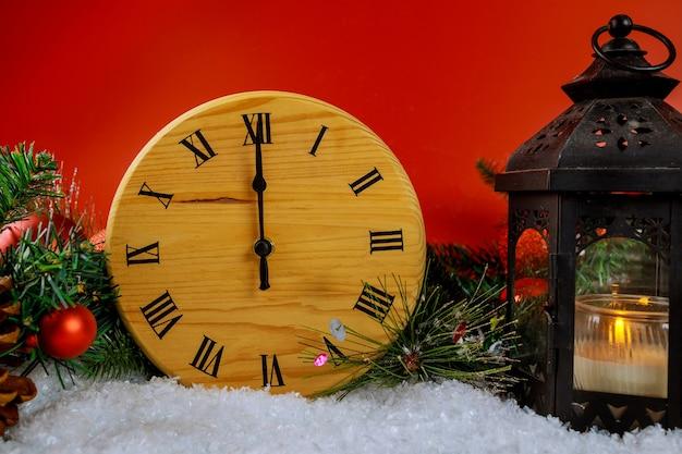 Nieuwjaar klok aftellen met kerst lantaarn op fir branch decoratie besneeuwde sparren tak rood Premium Foto