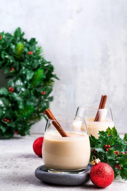 Nieuwjaar of kerstmis eierpunchcocktail, warme winter- of herfstdrank met kaneel en nootmuskaat in een glas op lichte steen, feestelijke decoratie Premium Foto