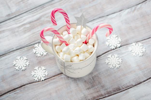 Nieuwjaar of kerstmis. samenstelling met marshmallows en snoep stokken op een houten achtergrond. Premium Foto