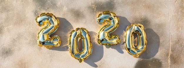 Nieuwjaar plat lag samenstelling. folieballonnen in de vorm van nummers 2020. Premium Foto