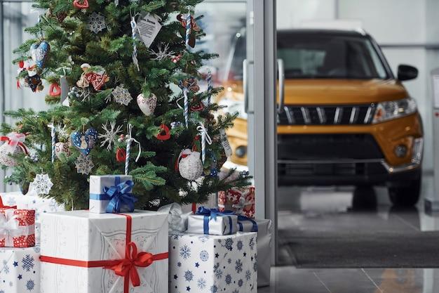 Nieuwjaar verfraaide automobiele salon met kerstmisboom en auto's Premium Foto