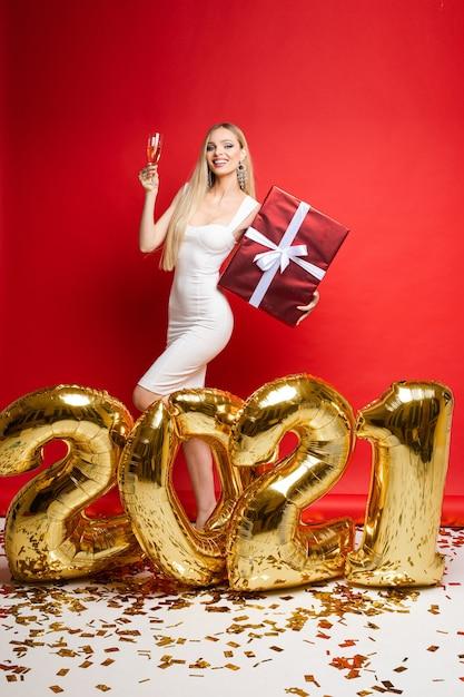 Nieuwjaar xmas vieren, glimlachend meisje met champagne, cadeau, gouden ballonnen in de vorm van 2021, confetti op rode muur. Premium Foto