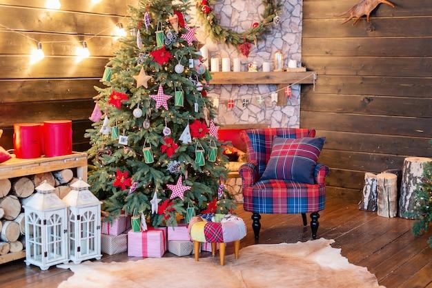 Nieuwjaars interieur, vakantie, kerstmis, gezellig en warm. kerstboom en open haard Premium Foto
