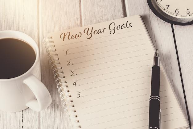 Nieuwjaarsdoelenlijst geschreven op notebook met wekker, pen en koffie Premium Foto