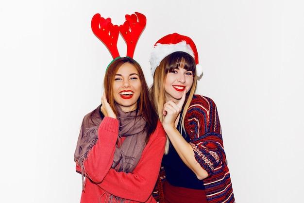 Nieuwjaarsfeest. twee mooie meisjes in grappige maskerade kerstmutsen sturen kus. indoor voorraad foto van beste vrienden poseren. isoleren. Gratis Foto