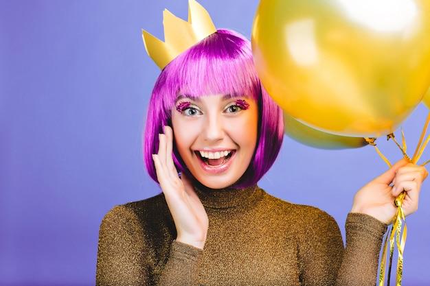 Nieuwjaarsfeeststemming van mooie grappige jonge vrouw met gouden ballonnen. knip paars haar, kroon, luxe jurk, heldere emoties, uiting van positiviteit, feest. Gratis Foto
