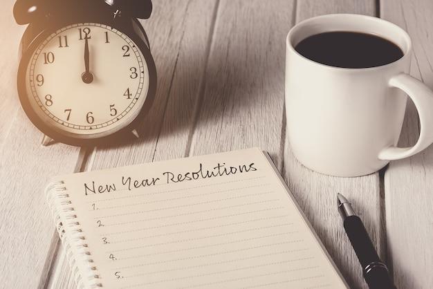 Nieuwjaarsresolutielijst geschreven op notebook met wekker, pen, koffie Premium Foto