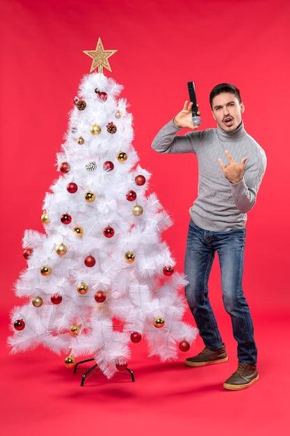 Nieuwjaarsstemming met positieve kerel die hiphoplied zingt dat zich dichtbij versierde kerstboom op rood bevindt Gratis Foto