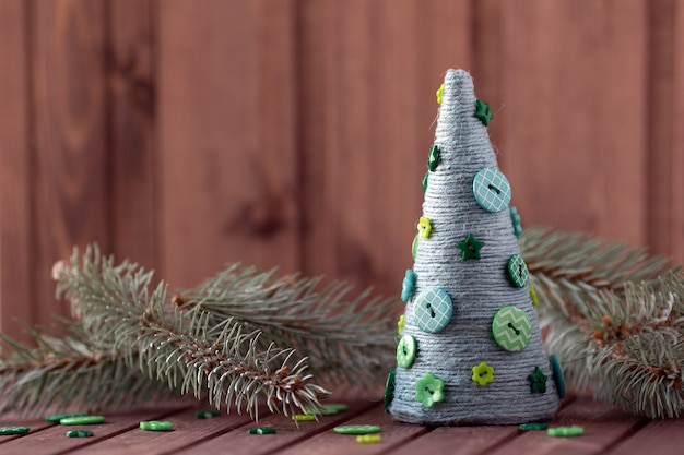 Nieuwjaarsstilleven met sparrenbrancard en handgemaakte kerstboom van touw en knopen. Premium Foto
