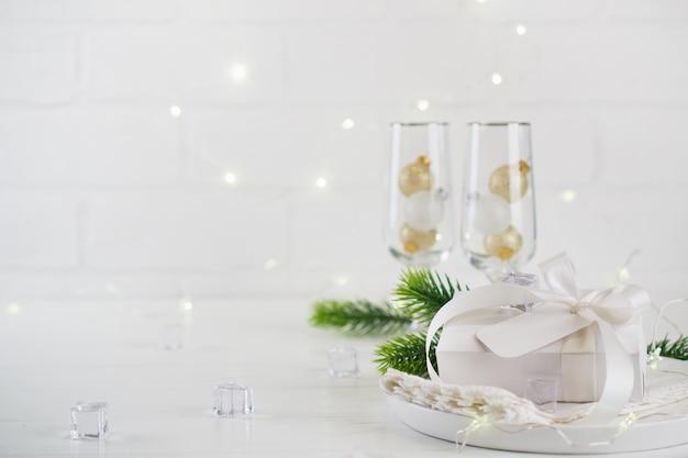 Nieuwjaarsviering. zilveren kersttafel met twee champagneglazen op de eettafel en geschenkdoos. met sterretjes Premium Foto