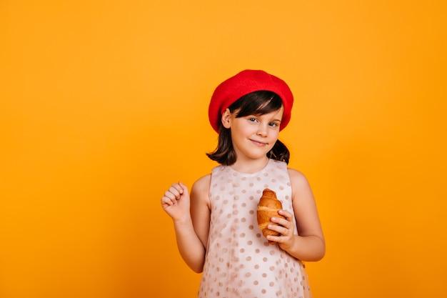 Nieuwsgierig donkerbruin jong geitje die zich voordeed op gele muur. preteen meisje croissant eten. Gratis Foto