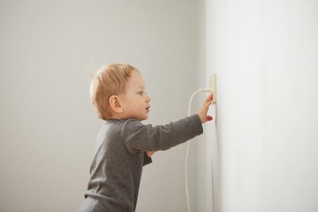 Nieuwsgierig jongetje spelen met stekker Gratis Foto