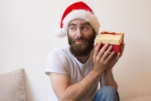 Nieuwsgierig man probeert te raden wat is in de doos van de gift van kerstmis Gratis Foto