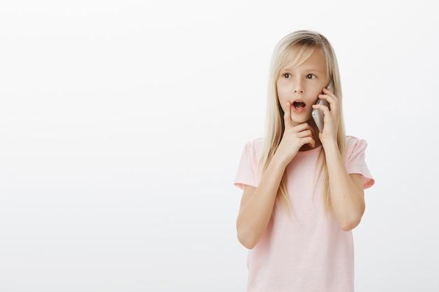 Nieuwsgierig slim blond meisje in roze t-shirt, praat op smarpthone en houdt vinger op lip, kaak laat vallen terwijl ze met interesse naar spreker luistert Gratis Foto