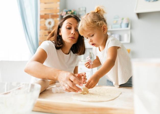Nieuwsgierig weinig dochter en moeder die koekjes voorbereiden Gratis Foto